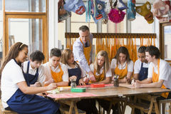 Scolari ed insegnante che si siedono intorno ad una tabella Fotografie Stock
