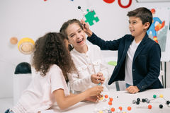 Scolari multietnici che lavorano con i modelli molecolari e che sorridono nella classe Immagine Stock