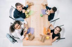 Scolari multietnici che mangiano pranzo mentre sedendosi alla tavola e sorridendo alla macchina fotografica Fotografia Stock
