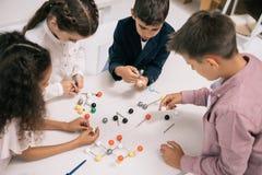 Scolari multietnici che studiano con i modelli molecolari alla lezione di chimica Fotografia Stock