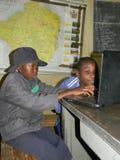 Scolari primari africani facendo uso del computer portatile alla scuola Immagine Stock