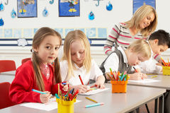 Scolari primari ed insegnante che hanno una lezione Immagini Stock