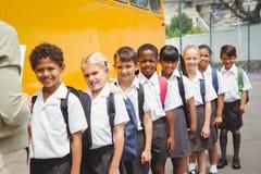 Scolari svegli che aspettano per salire scuolabus Fotografia Stock