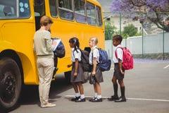 Scolari svegli che aspettano per salire scuolabus Fotografie Stock