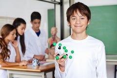 Scolaro adolescente che tiene struttura molecolare dentro Fotografie Stock Libere da Diritti