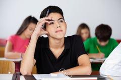 Scolaro adolescente premuroso che si siede allo scrittorio Fotografie Stock Libere da Diritti