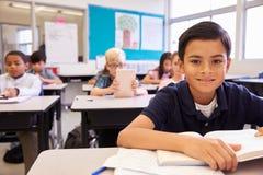 Scolaro allo scrittorio in una scuola elementare che guarda alla macchina fotografica Immagini Stock Libere da Diritti