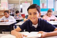 Scolaro allo scrittorio in una scuola elementare che guarda alla macchina fotografica Fotografia Stock