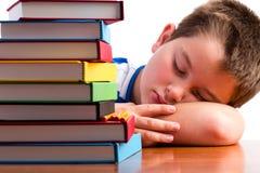 Scolaro annoiato o sovraccarico addormentato sul suo scrittorio Immagini Stock