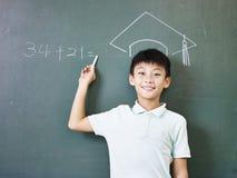 Scolaro asiatico che sta sotto un cappello di laurea gesso-disegnato Fotografia Stock