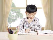 Scolaro asiatico che studia a casa Immagini Stock Libere da Diritti