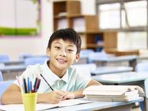 Scolaro asiatico che studia nell'aula Fotografia Stock