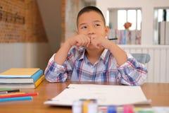 scolaro asiatico del bambino del ragazzo del bambino che pensa mentre disegnando immagine CH immagine stock libera da diritti