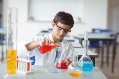 Scolaro attento che fa un esperimento chimico in laboratorio Immagini Stock