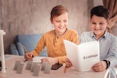 scolaro Bionda-dai capelli che fa le note mentre studiando ecologia fotografie stock