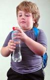 Scolaro biondo sveglio con una bottiglia di acqua Immagine Stock