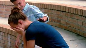 Scolaro che consola il suo amico triste sui punti in città universitaria video d archivio
