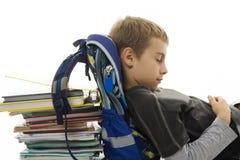 Scolaro che dorme sul sacchetto e sui libri di banco. Fotografie Stock