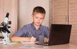 Scolaro che fa le sue note di scrittura di progetto di compito della scuola, micro immagine stock