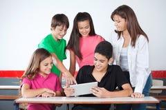 Scolaro che indica alla compressa con i compagni di classe dentro Fotografia Stock Libera da Diritti