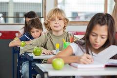 Scolaro che si siede allo scrittorio con i compagni di classe in una fila Fotografia Stock Libera da Diritti
