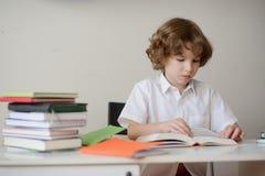 Scolaro che si siede allo scrittorio e che legge un libro Immagini Stock
