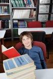 Scolaro che si siede con i libri impilati alla Tabella Immagini Stock