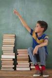 Scolaro che si siede sulla pila di libro davanti alla lavagna in aula Immagini Stock