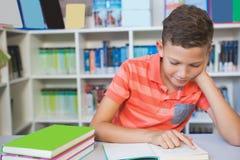 Scolaro che si siede sulla tavola e sul libro di lettura in biblioteca Immagini Stock