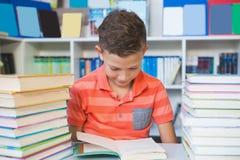 Scolaro che si siede sulla tavola e sul libro di lettura in biblioteca Fotografie Stock