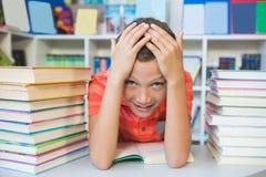 Scolaro che si siede sulla tavola e sul libro di lettura in biblioteca Fotografia Stock Libera da Diritti