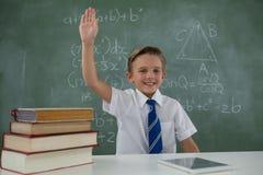 Scolaro che solleva mano mentre sedendosi nell'aula Fotografia Stock
