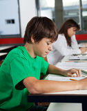Scolaro che studia allo scrittorio in aula Fotografia Stock