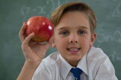 Scolaro che tiene mela rossa contro la lavagna Immagine Stock Libera da Diritti