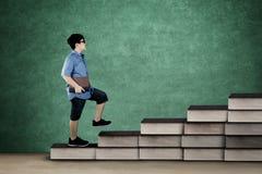 Scolaro che tiene un libro sulla scala dei libri Fotografia Stock Libera da Diritti