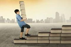 Scolaro che tiene un mucchio dei libri sulla scala Fotografia Stock