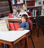 Scolaro con i libri che si siedono alla biblioteca Fotografia Stock