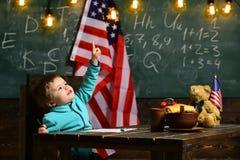 Scolaro con la bandiera di U.S.A., lavagna verde nella scuola, festa dell'indipendenza del fondo Fotografia Stock