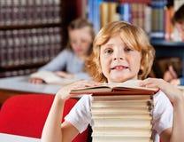 Scolaro con la pila di libri che si siedono nella biblioteca Immagini Stock Libere da Diritti