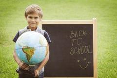 Scolaro con un globo contro la lavagna Istruzione di nuovo al concetto della scuola Immagini Stock