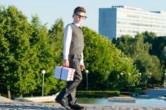 Scolaro del ragazzo che cammina giù la via, con un mucchio dei libri di scuola per la scuola Immagini Stock Libere da Diritti
