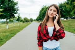 Scolaro della ragazza in una camicia rossa, di estate nei supporti della città sulla strada Chiamate ai genitori ed alle amiche O fotografie stock libere da diritti