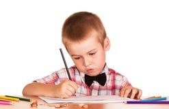 Scolaro diligente che si siede alla tavola, pitture in album Fotografie Stock