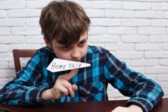 Scolaro disubbidiente impertinente che fa aereo di carta del suo tas della casa Immagine Stock Libera da Diritti