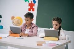 Scolaro e scolara che utilizza le compresse digitali mentre sedendosi allo scrittorio nell'aula Fotografia Stock Libera da Diritti