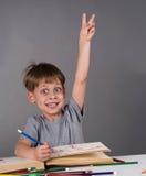 Scolaro entusiasta che solleva la sua mano per dare una risposta, concetto di istruzione Immagine Stock