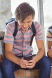 Scolaro felice che si siede sul davanzale della finestra e che utilizza telefono cellulare nel corridoio Immagini Stock
