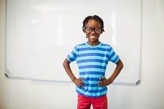 Scolaro felice che sorride nell'aula con la mano sull'anca Immagini Stock Libere da Diritti