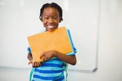Scolaro felice che tiene un libro in aula Fotografia Stock Libera da Diritti