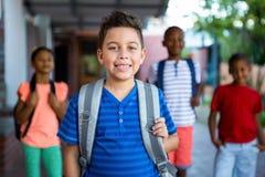 Scolaro felice con i compagni di classe al corridoio della scuola Immagine Stock